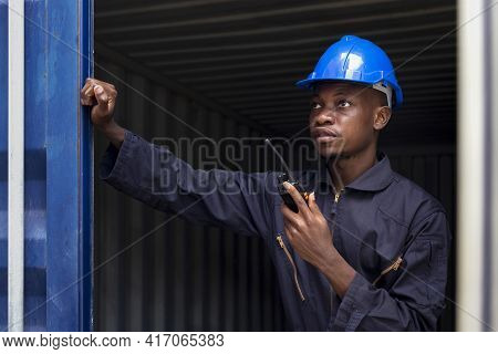 Black African Amarican Man Worker Working Control Loading Freight Containers At Commercial Shipping
