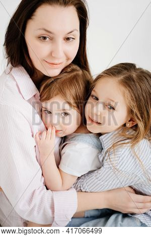 Happy Family Sit On Floor And Cuddle In White Photo Studio.mom And Two Daughters