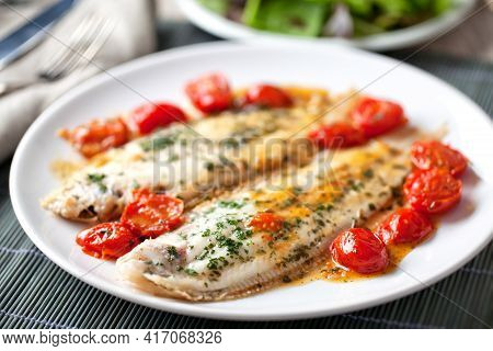 Sole With Cherry Tomatoes On A Plate. High Quality Photo.