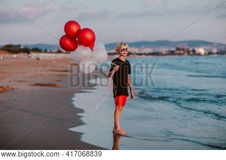 Blond Cute Teen Boy With Face Painting Like A Clown In Summer Shorts And Shirt Posing With Bunch Of