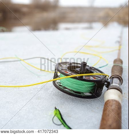 Winter Fly Fishing Picture. Fly Rod And Reel On Snowy River Bank.