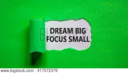 Dream Big Focus Small Symbol. Concept Words 'dream Big Focus Small' Appearing Behind Torn Green Pape