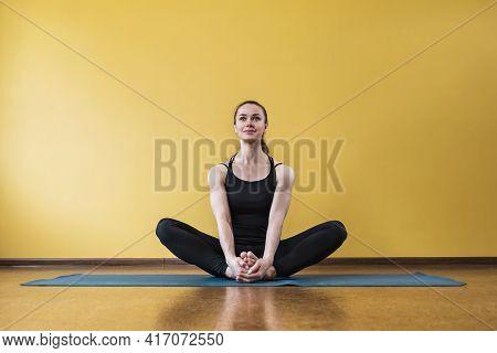 Satisfied Woman Practicing Yoga, Doing Buddha Konasana Exercise, Butterfly Pose, Exercising Sitting
