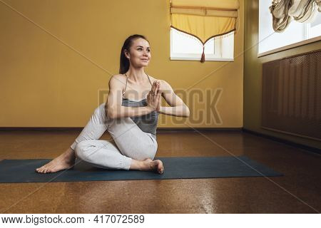 Beautiful Young Woman In White Pants And A Gray Top, Practicing Yoga, Performs The Ardha Matsyendras