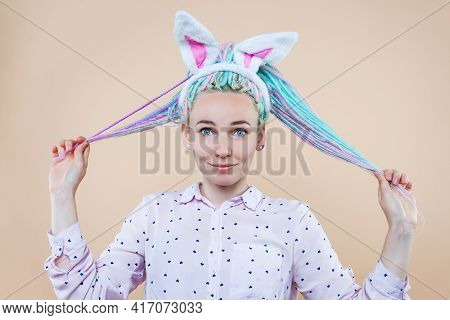 Pretty Cute Girl In Bunny Ears, Pink Shirt Is Smiling. Young Woman With Colored Dreadlocks Is Prepar