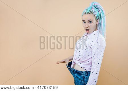 Closeup Of Slim Waist Of Young Woman Standing In Big Jeans Showing Successful Weight Loss, Indoor St