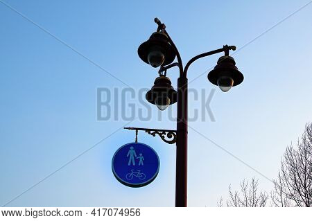 Classic Older Lamp With Pedestrian And Bicycle Share Pathway Sign. Blue Sky Background. Blue Road Si