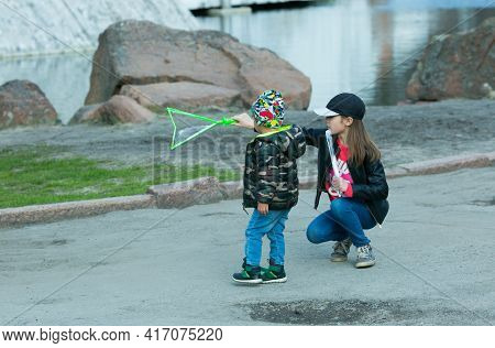 Dnepropetrovsk, Ukraine - 04.10.2021: Cheerful Cute Children Blowing Soap Bubbles In A Park In Natur