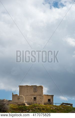 Abandoned And Deserted House At The Top Of A Hill Against Stormy Cloudy Sky.