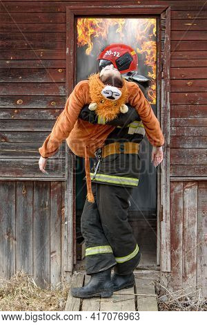 The Rescuer Carries The Child Out Of The Burning Old House.