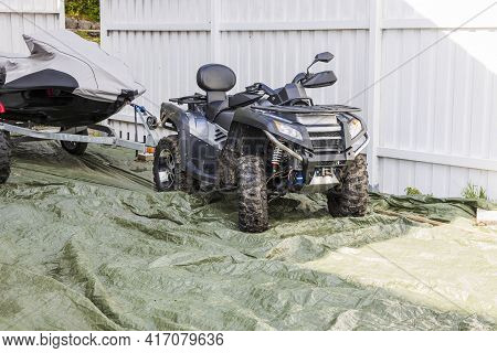 Close Up View Of Off Road Vehicle With Water Scooter With A Scooter On Trailer On White Fence Backgr