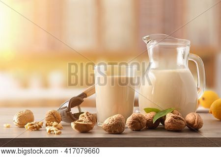 Glass And Jug Full Of Nutty Vegetable Drink. With Walnuts On The Table And Rustic Kitchen Background