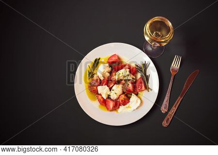 Caprese Salad And Glass Of White Wine On Dark Background. Top View With Copy Space.