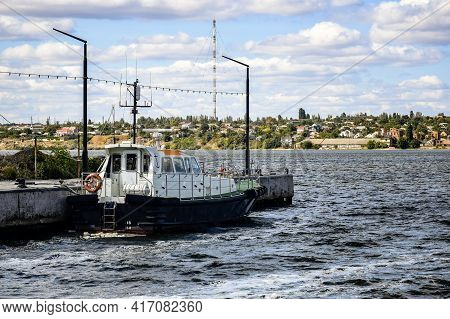 Small River Tug Is Moored At The Pier Against The Background Of The River, Coast And Cloudy Sky. Sel