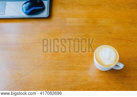 Wood Office Desk Table With Cup Of Latte Coffee And Laptop Computer. A Cup Of Latte In A Cafe
