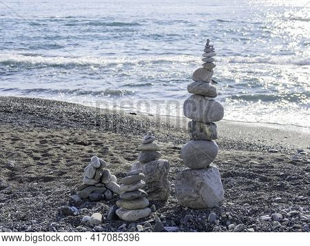 Pyramid Of Pebbles And Stones On Beach. Sunny Day At Seaside. Leisure On Ocean Coast.