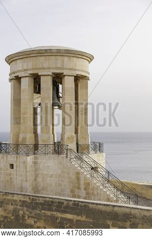 Siege Bell War Memorial Monument On Cloudy Sky And Surface Mediterranean Sea Background. Architectur