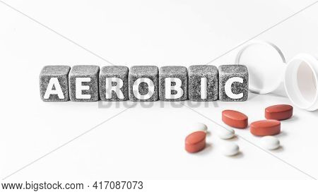 Word Aerobic Is Made Of Stone Cubes On A White Background With Pills. Medical Concept Of Treatment,