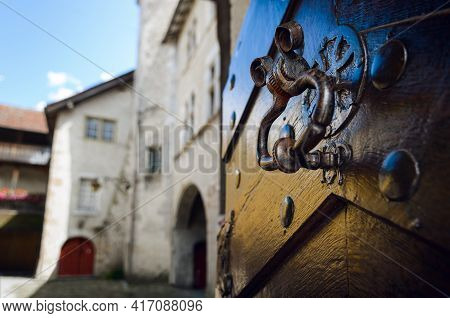 Ancient Ring Shaped Metal Knocker On A Wooden Studded Door With Signs Of Aging And Weather