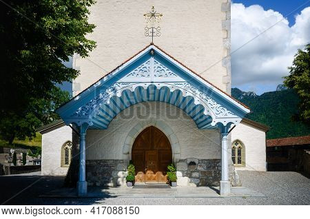 Blue Wooden Front Porch And Entrance Of The Church Of Saint Theodule In Gruyeres, Famous Cheese Maki