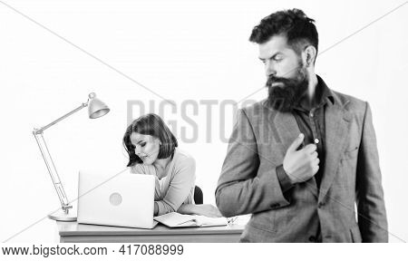 Working Together. Manager Boss Stand In Front Of Girl Busy With Laptop. Office Manager Or Secretary.