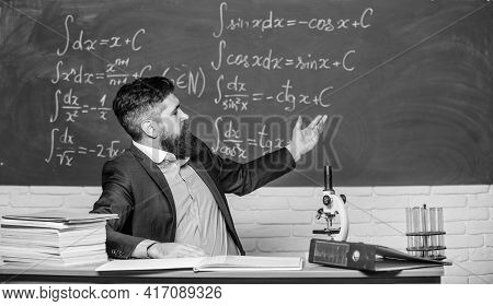 Teacher Charismatic Hipster Sit At Table Classroom Chalkboard Background. Educational Conversation.