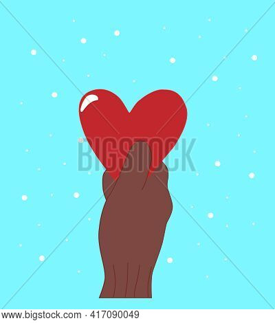 A Hand In A Knitted Warm Glove Holds A Red Heart On A Blue Background With Snowflakes. Valentine's D