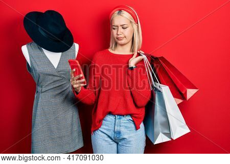 Beautiful blonde woman holding shopping bags and smartphone skeptic and nervous, frowning upset because of problem. negative person.