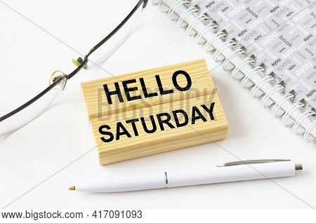 Text Hello Saturday On A Wooden Blocks Lying Near Notepad With Eyeglasses And Pen. Could Be For Busi