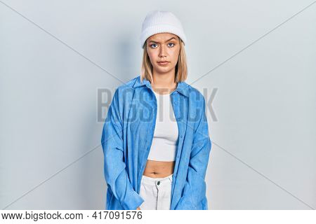 Beautiful blonde woman wearing wool hat skeptic and nervous, frowning upset because of problem. negative person.
