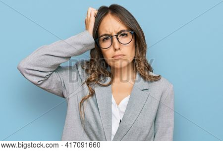 Young brunette woman wearing business clothes confuse and wonder about question. uncertain with doubt, thinking with hand on head. pensive concept.