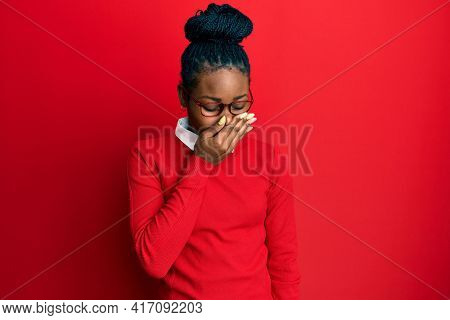Young african american woman wearing casual clothes and glasses smelling something stinky and disgusting, intolerable smell, holding breath with fingers on nose. bad smell