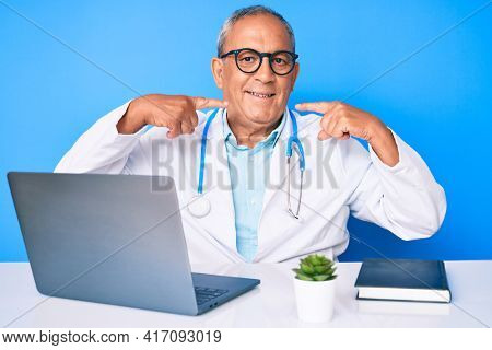 Senior handsome man with gray hair wearing doctor uniform working using computer laptop smiling cheerful showing and pointing with fingers teeth and mouth. dental health concept.