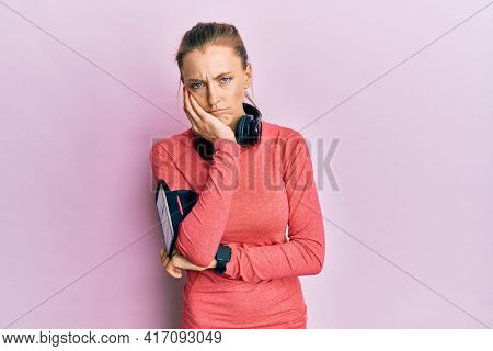 Beautiful caucasian woman wearing sportswear and arm band thinking looking tired and bored with depression problems with crossed arms.