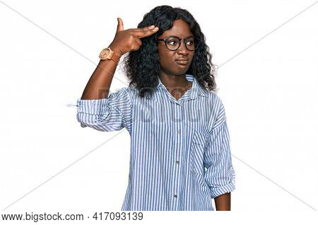 Beautiful african young woman wearing casual clothes and glasses shooting and killing oneself pointing hand and fingers to head like gun, suicide gesture.