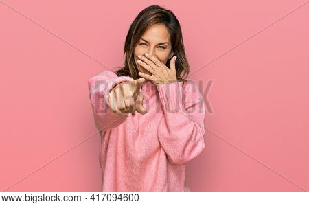Young hispanic woman wearing casual clothes laughing at you, pointing finger to the camera with hand over mouth, shame expression