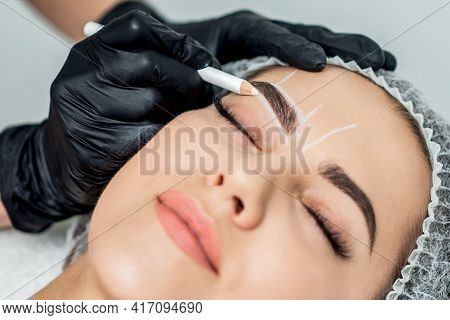 Markup With Pencil On Eyebrows Of Yong Woman While Permanent Make Up.