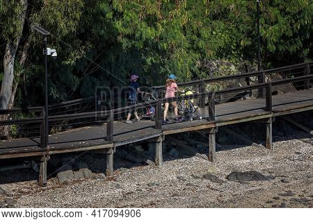 Airlie Beach, Queensland, Australia - April 2021: Two Young Mothers Pushing Babies In Prams Along Ti