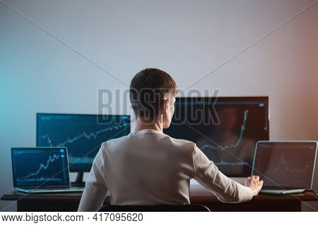 Back View Of Male Trader Looking At Monitor With Stock Exchange Graph Or Chart
