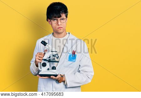Handsome hipster young man wearing lab coat holding microscope skeptic and nervous, frowning upset because of problem. negative person.