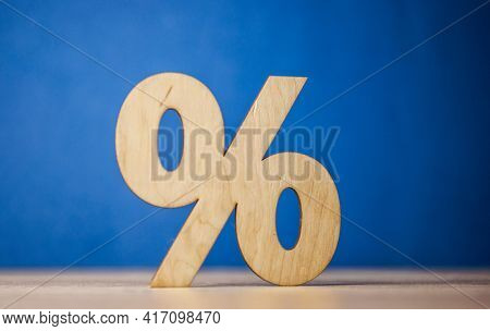Percentage sign symbol icon wooden on wood table against blue wall background