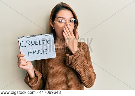 Young caucasian woman holding cruelty free message paper covering mouth with hand, shocked and afraid for mistake. surprised expression