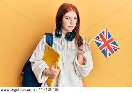 Young red head girl exchange student holding uk flag skeptic and nervous, frowning upset because of problem. negative person.