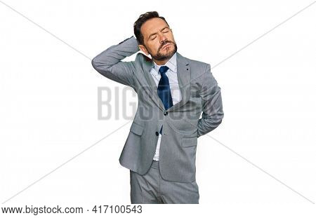 Middle age man wearing business clothes suffering of neck ache injury, touching neck with hand, muscular pain