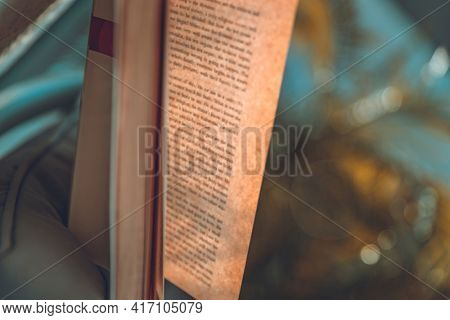 Closeup Photo of an Open Book in Sunny Day on Tropical Background. Relaxation on the Beach with Good Novel. Peaceful Summer Vacation.