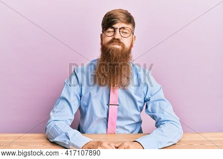 Young irish redhead man wearing business shirt and tie sitting on the table puffing cheeks with funny face. mouth inflated with air, crazy expression.