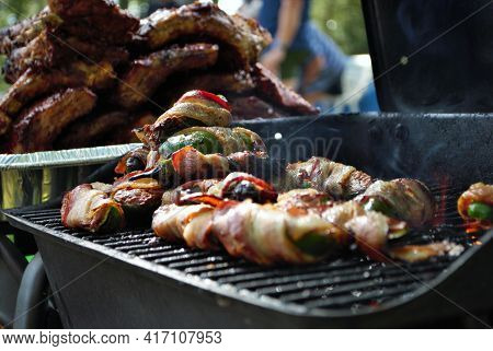 Ribs And Bacon Wrapped Jalapenos On The Grill At A Backyard Cookout
