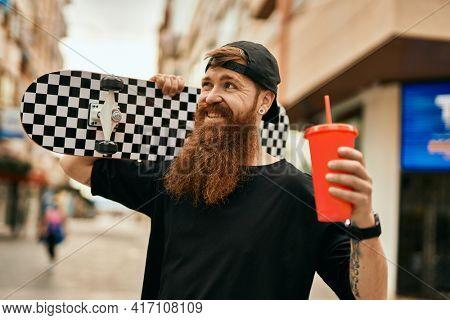 Young irish skater man holding skate and drinking soda at the city.