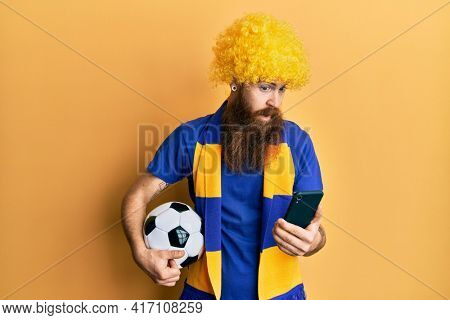 Redhead man with long beard football hooligan cheering game holding smartphone clueless and confused expression. doubt concept.