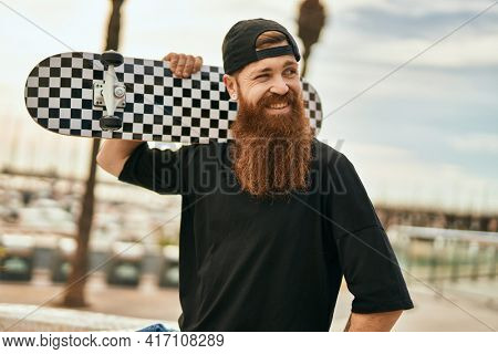 Young irish skater man smiling happy holding skate at the city.